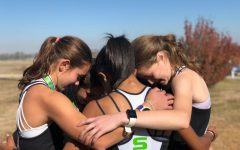 The Girls Cross Country Team gather for one last team huddle after finishing their final race of the season