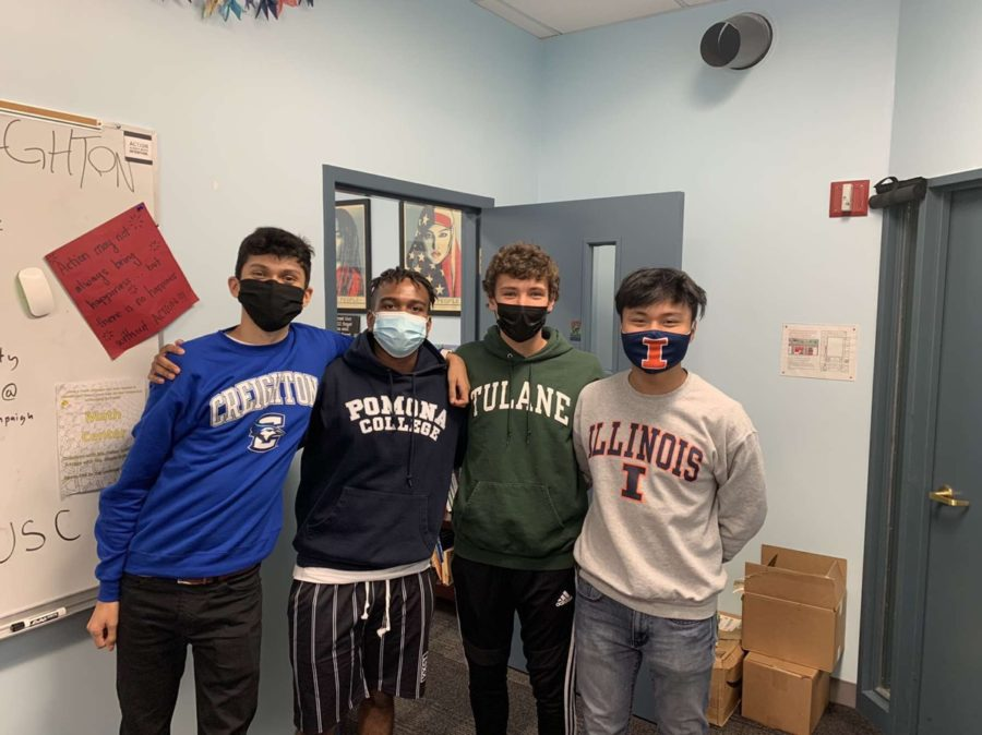 Seniors pose for a photo wearing apparel from their respective colleges.